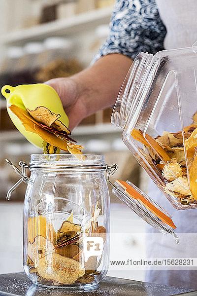 Nahaufnahme einer Person  die in einer Küche steht und Trockenobstscheiben in ein Glasgefäß legt. Nahaufnahme einer Person, die in einer Küche steht und Trockenobstscheiben in ein Glasgefäß legt.