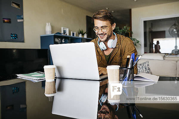 Smiling man working on table at home using laptop