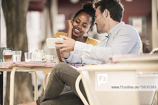 Glückliches junges Paar mit Handy in einem Café im Freien