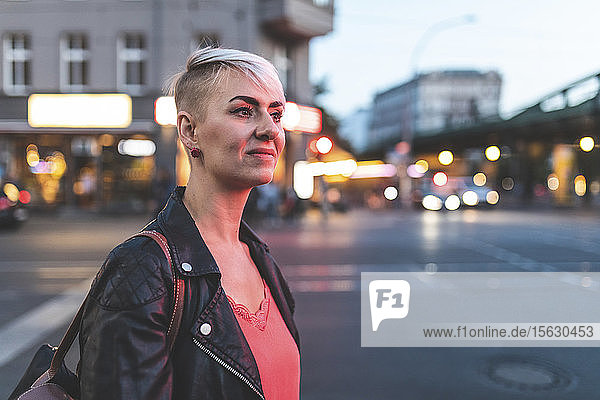 Portrait of smiling blond woman at roadside in the evening  Berlin  Germany
