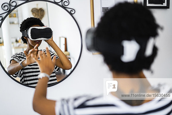 Young woman with VR glasses in front of a mirror at home