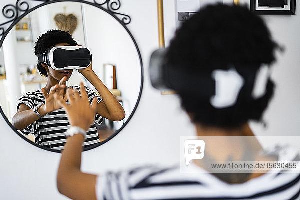 Junge Frau mit VR-Brille vor dem Spiegel zu Hause