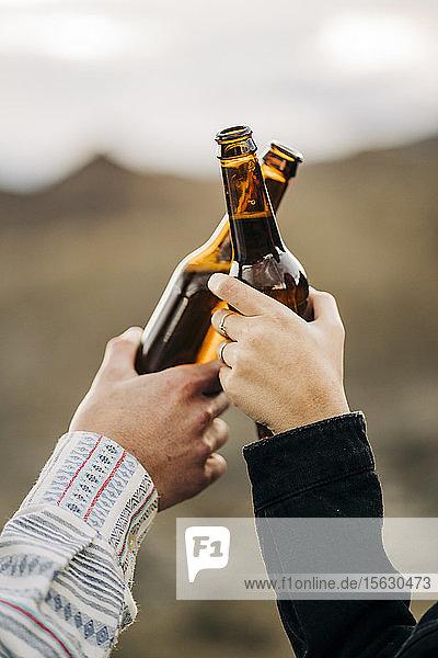 Nahaufnahme eines Paares klirrender Bierflaschen
