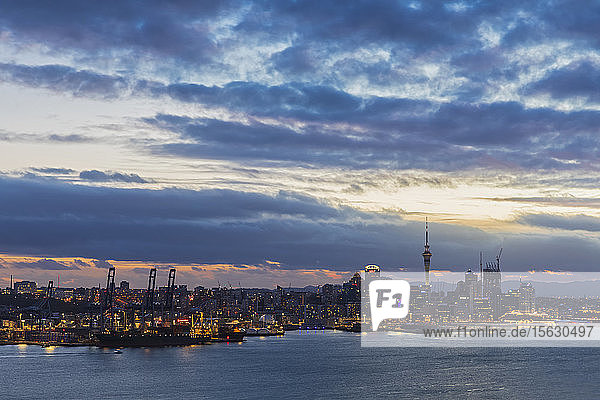 Modern buildings by sea against cloudy sky at dusk in Auckland  New Zealand