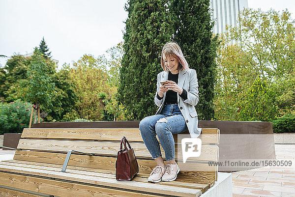 Lächelnde Frau sitzt auf Parkbank und benutzt Mobiltelefon