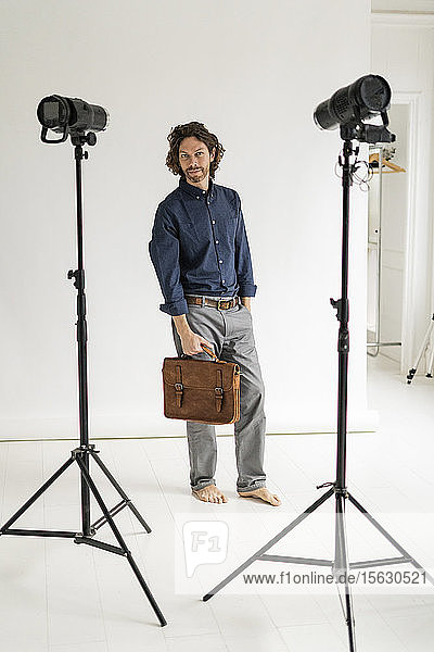 Portrait of a photographer holding a bag in his studio