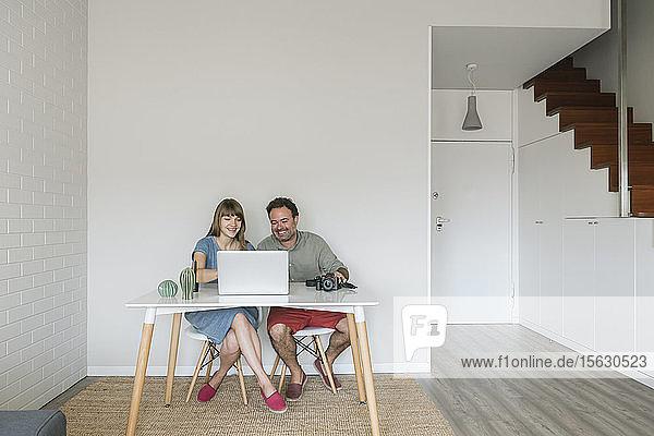 Lachende Frau und lachender Mann sitzen zusammen am Schreibtisch und schauen auf den Laptop