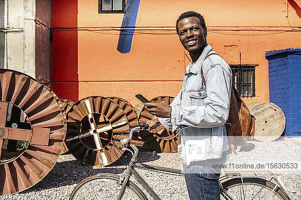 Entspannte junge Leute pendeln in der Stadt mit dem Hos-Fahrrad  mit Smartphone