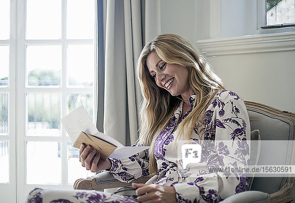Frau liest Brief  auf Couch sitzend
