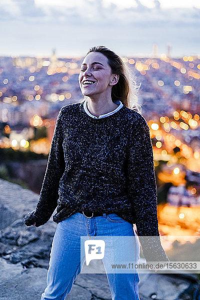 Glückliche junge Frau im Morgengrauen über der Stadt  Barcelona  Spanien