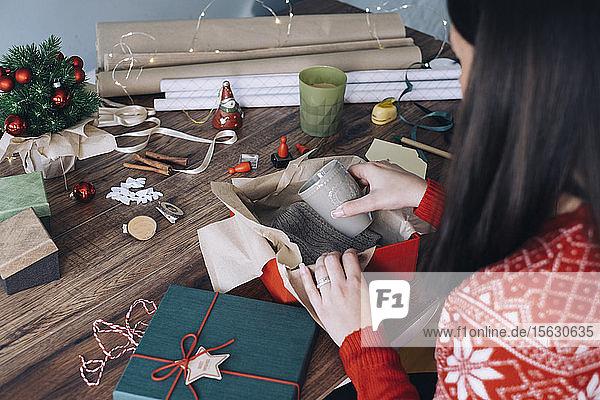 Frauenhände packen Weihnachtsgeschenk ein
