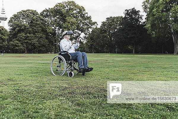 Senior man sitting in wheelchairin a park using Virtual Reality Glasses