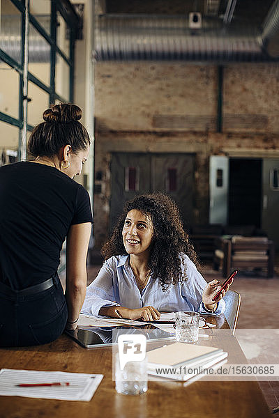 Two young businesswomen with smartphone in loft office