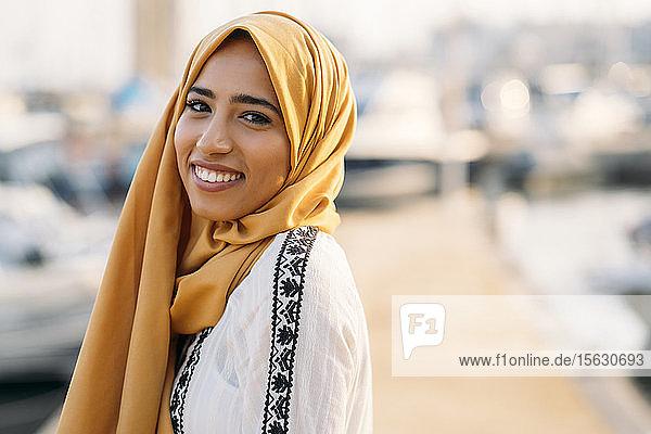 Junge muslimische Frau mit gelbem Hidschab beim Spaziergang am Hafen