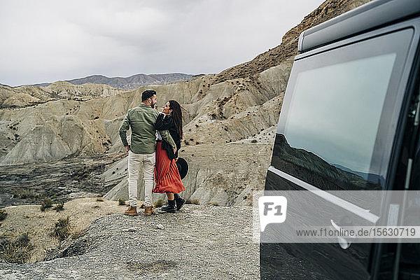 Junges Paar in Wüstenlandschaft unter bewölktem Himmel neben dem Wohnmobil  Almeria  Andalusien  Spanien
