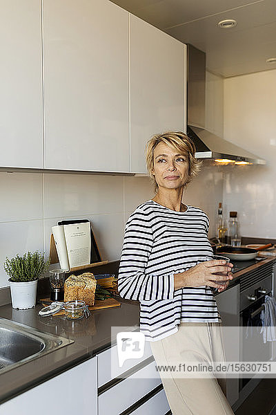 Mature woman relaxing in kitchen at home