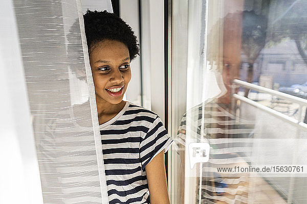 Young woman at home looking out of window