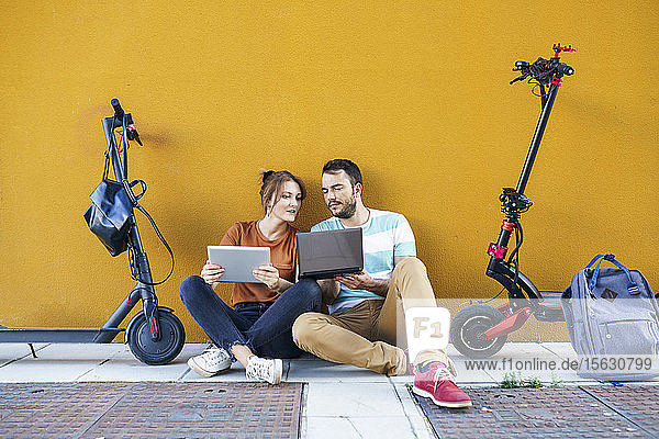 Portrait of couple with backpacks and electric scooters using laptop and digital tablet