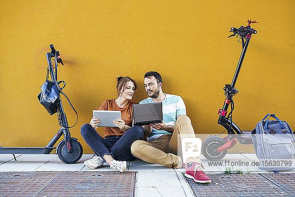 Portrait eines Paares mit Rucksäcken und Elektrorollern mit Laptop und digitalem Tablet
