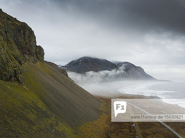 Iceland  Empty road between rough mountains and shore of Jokulsarlon