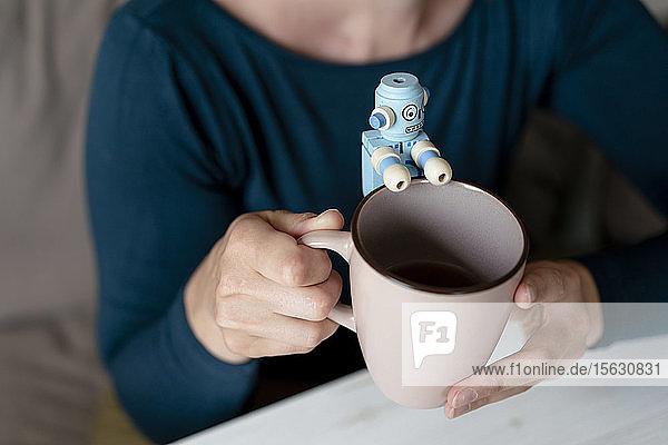 Frauenhände halten Becher mit kleinem Roboter