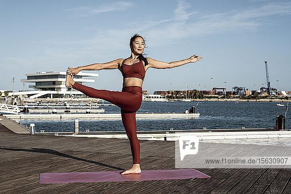 Asiatische Frau  die Yoga praktiziert  auf einem Bein stehend  Hand-zu-Groß-Zehen-Haltung Asiatische Frau, die Yoga praktiziert, auf einem Bein stehend, Hand-zu-Groß-Zehen-Haltung