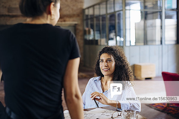 Two young businesswomen at table in loft office