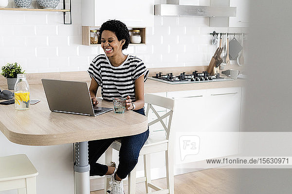 Happy young woman using laptop at home