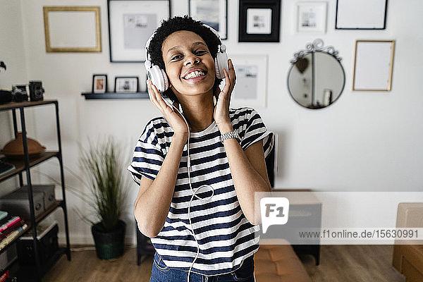 Glückliche junge Frau  die zu Hause mit Kopfhörern Musik hört