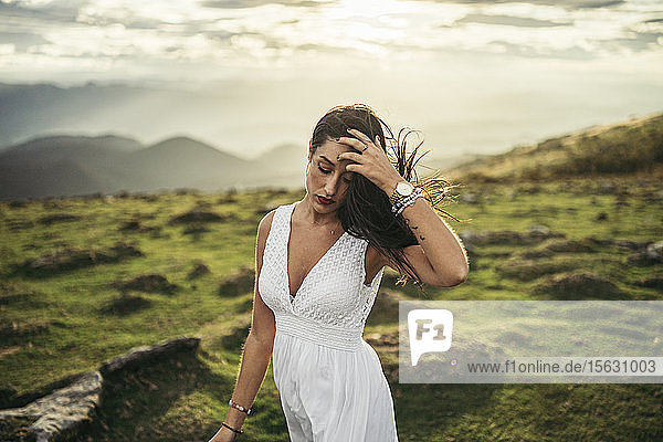 Young woman wearing white dress on viewpoint at sunset