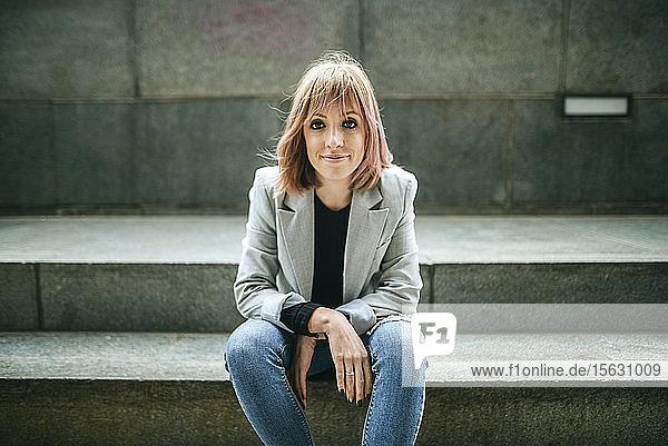 Porträt einer selbstbewussten Frau  die auf einer Treppe sitzt