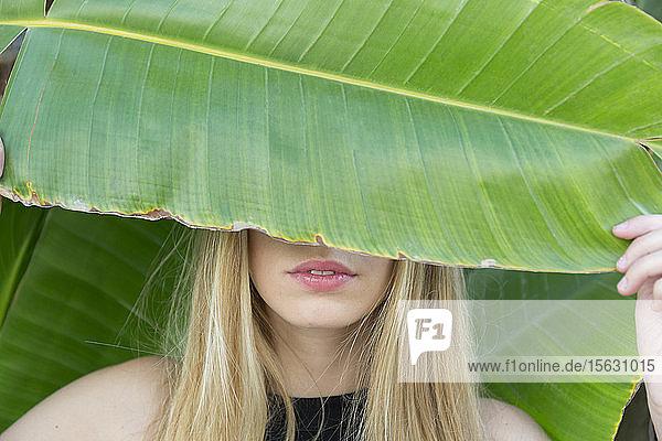 Blonde junge Frau  die Augen mit großem Blatt bedeckt  Nahaufnahme