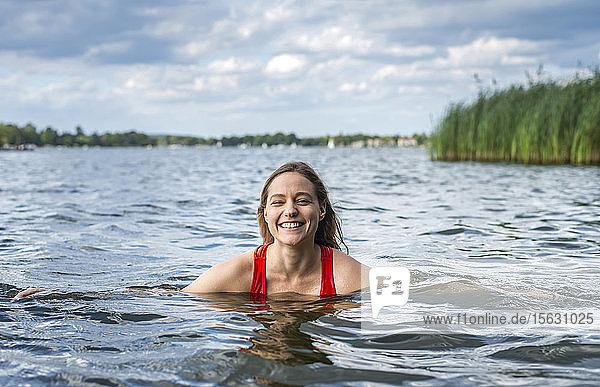 Porträt einer lächelnden Frau beim Baden in einem See