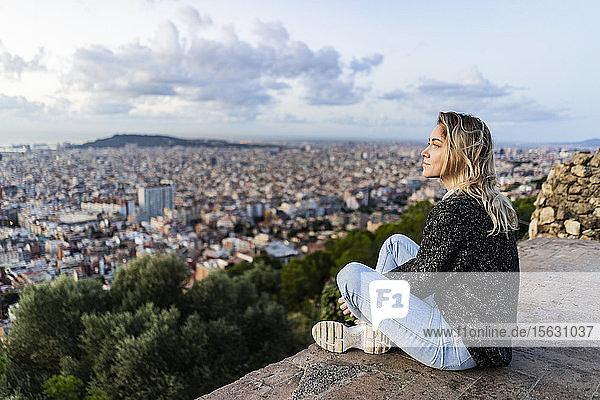 Junge Frau sitzt bei Sonnenaufgang über der Stadt  Barcelona  Spanien