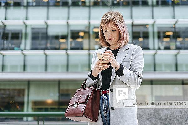 Frau benutzt Mobiltelefon in der Stadt