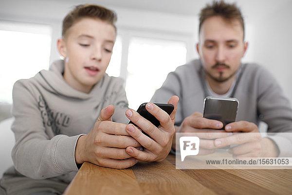 Junger Mann und Teenager benutzen Smartphones im Wohnzimmer