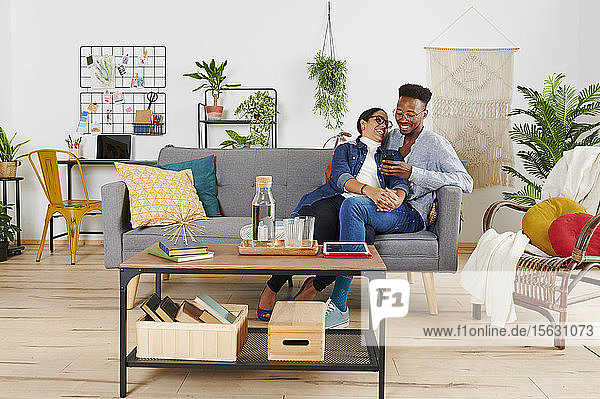 Multiethnic couple spending time together at living room and using smartphone