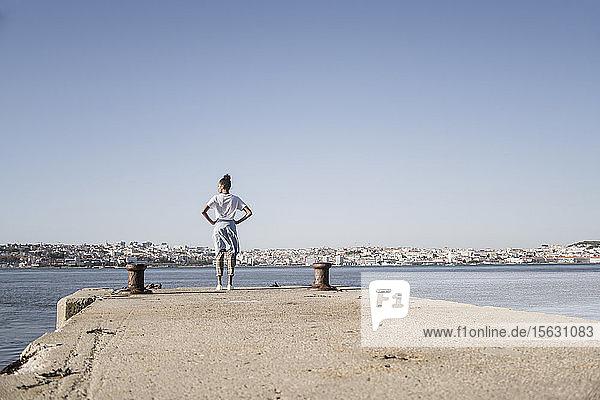 Junge Frau steht am Pier am Wasser  Lissabon  Portugal