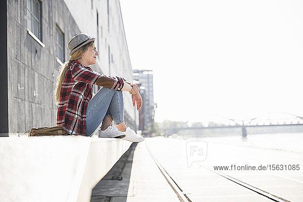 Junge Frau mit Hut  die sitzt und in die Ferne schaut