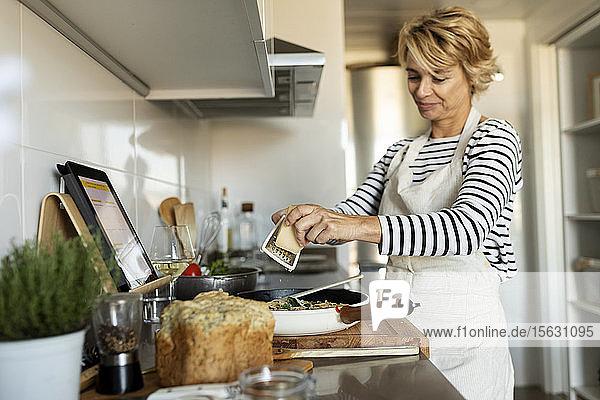 Reife Frau mit Tablette kocht Nudelgericht in der heimischen Küche