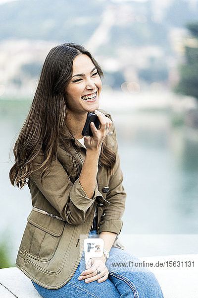 Young brunette woman using smartphone and laughing in Verona  Italy