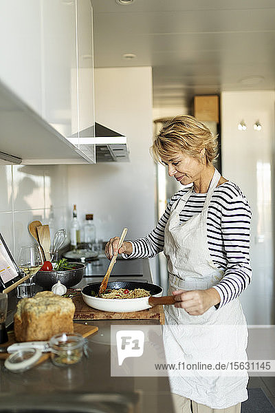 Mature woman cooking pasta dish in kitchen at home