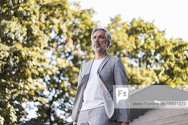 Modisch reifer Geschäftsmann geht in der Stadt die Treppe hinunter