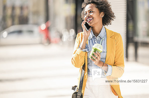 Glückliche junge Frau am Telefon in der Stadt