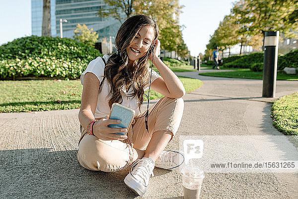 Junge Frau sitzt im Park mit einem Smartphone und hört Musik mit Kopfhörern