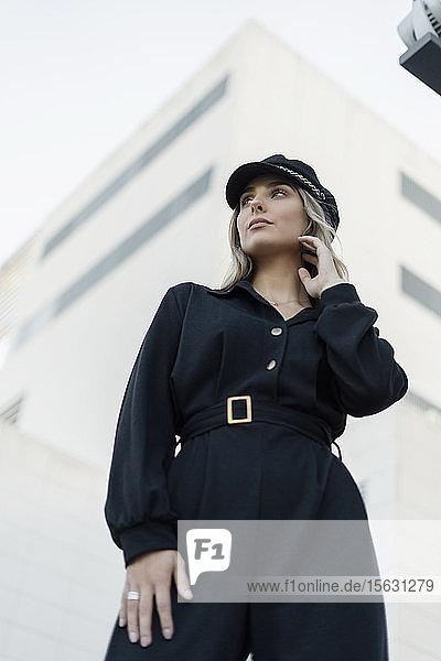 Junge blonde Geschäftsfrau mit schwarzer Matrosenmütze  seitwärts blickend  niedriger Blickwinkel