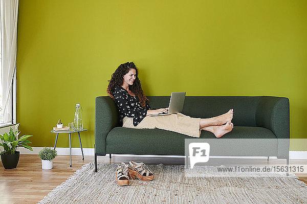 Lächelnde junge Geschäftsfrau mit Laptop auf der Couch im modernen Büro