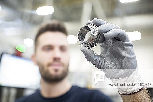 Nahaufnahme eines Mannes  der ein Werkstück in einer Fabrik hält
