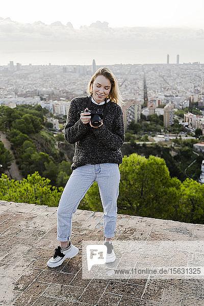 Junge Frau mit Kamera über der Stadt bei Sonnenaufgang  Barcelona  Spanien