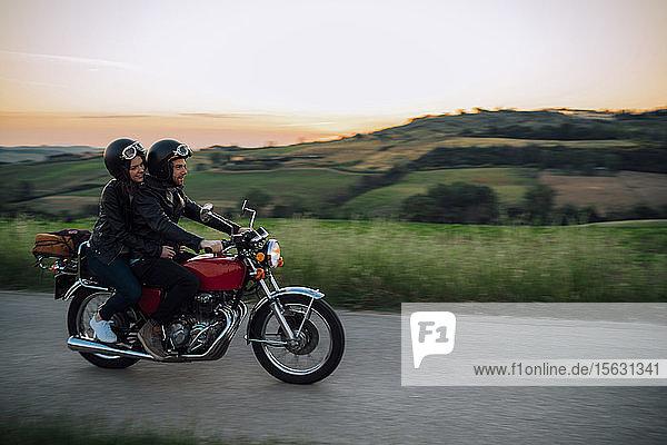Junges Paar mit einem Oldtimer-Motorrad auf einer Landstraße bei Sonnenuntergang  Toskana  Italien